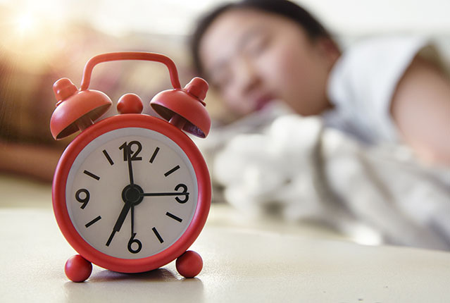 Sleeping Teenage girl with Alarm Clock